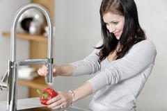 woman rinsing peppers in a sink - stock photo