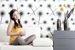 Woman relaxing on her sofa with a drink Stock Photos