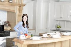 woman preparing a meal in the kitchen - stock photo