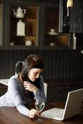 Woman on a laptop in kitchen Stock Photos