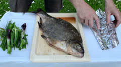 Bream fish prepared for bake in fire bonfire ember cinder foil Stock Footage