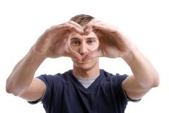 Young man drawing heart with hands Stock Photos