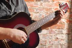 Playing on acoustic guitar Stock Photos