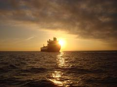 Oil Tanker Sunrise Open Ocean Commerce Economy Petroleum Economy - stock photo