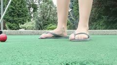 Mini golf putting in sandals Stock Footage