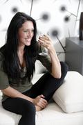 woman relaxing on her sofa with a drink - stock photo