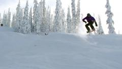 woman making a jump while Snowboarding on a Ski Resort at Canadian Mountains - stock footage