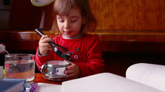 Baby Girl Looks through Magnifier to Clock Stock Footage