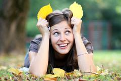 Stock Photo of woman lying on a carpet of leaves in autumn park