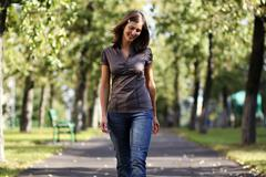 full length, walking woman in blue jeans - stock photo