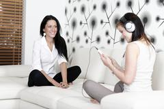 Two friends listening to music Stock Photos