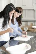 two friends looking at recipes - stock photo