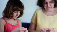 Stock Video Footage of granddaughter and grandmother knitting  at home