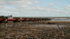 Sewage pipe out to sea beach Stock Footage
