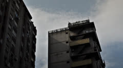 Clouds moving over socialist looking buildings during the day in the city center Stock Footage