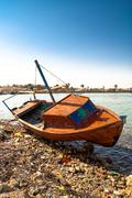 Red rowboat lying at shore - stock photo
