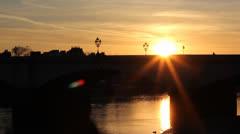 London Bus passes through setting sun on bridge Stock Footage