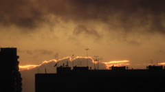 Dark town building silhouettes at background lights on the clouds border Stock Footage