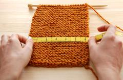 Two hands measuring knitting in inches Stock Photos