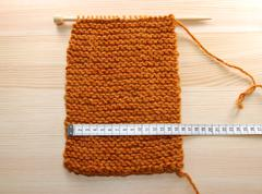A length of knitting being measured in centimetres Stock Photos