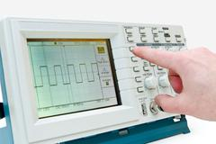 Engineer operating a digital oscilloscope Stock Photos