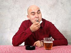 Stock Photo of beer drinker lighting up a cigarette