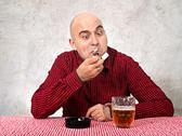 Stock Photo of beer drinker lighting up a cigarette