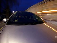 Car Driving Through City at Night, Streaming Lights - Gopro POV Shot - stock photo