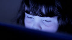 Child browsing interent, face lit by computer screen Stock Footage