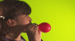 Girl inflates balloon side view Stock Footage