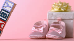 Baby blocks toppling over in front of booties and gift box Stock Footage