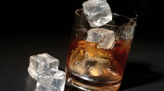 Ice cubes falling into tumbler of whiskey and ice Stock Footage