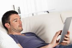 tablet on sofa at home - stock photo