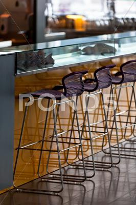Stock photo of empty row of stools at a bar