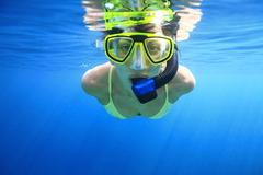 Woman snorkeling in the blue Stock Photos