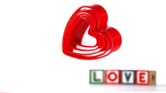 Heart ornaments falling with blocks spelling love in background Stock Footage