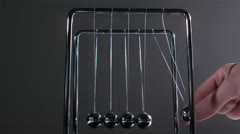 Finger pushing newtons cradle Stock Footage