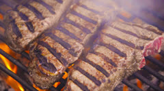Steaks grilling over hot flames Stock Footage