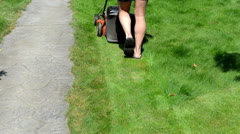 Fast man in shorts flip-flop shoes mower cut grass stone path Stock Footage