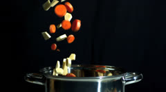 Sliced carrot and parsnip falling into saucepan on black background - stock footage