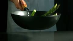 Chef tossing wok of asparagus Stock Footage