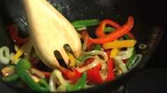 Wooden fork mixing vegetables in wok Stock Footage