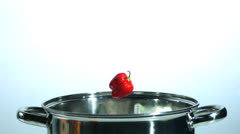 Red chili falling in a pot Stock Footage