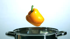 Stock Video Footage of Yellow pepper falling in saucepan