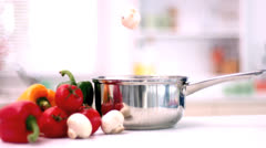 Mushrooms falling into a saucepan in kitchen Stock Footage