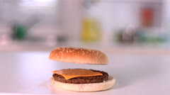 Bun falling on cheese burger in kitchen Stock Footage