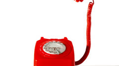 Stock Video Footage of Receiver falling onto red dial phone on white background
