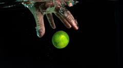 Stock Video Footage of Hand grabbing lime from water