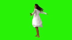 Girl in white dress twirling on green screen Stock Footage