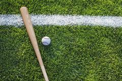 baseball bat and ball on grass field viewed from above - stock photo